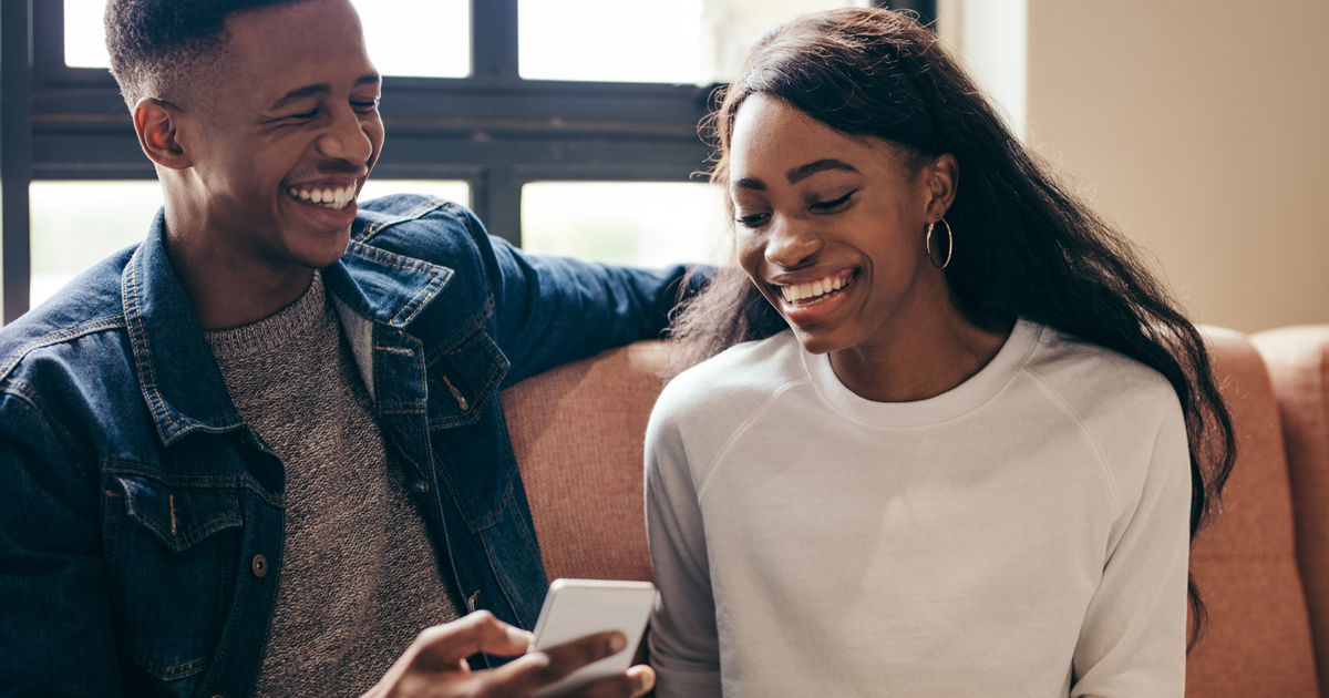 Young man and woman smiling at phone.